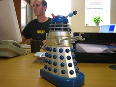 The Dalek Desk Protector roams your desk autonomously and turns whenever it reaches an obstacle or the edge, calling out 'Exterminate' as it turns. Perfect for frightening off pesky pen-stealers and the like! Desk Gadgets, Fun Gadgets, Office Gadgets, The Brightside, Desk Protector, Innovative Ideas, Cool Gear, Dalek, Stationary