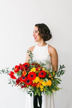 Colorful modern wedding editorial at Dobbin St in Williamsburg Brooklyn designed by Florist Michelle Edgemont Design. Red anemone and yellow ranunculus bouquet.