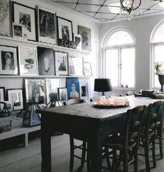 Wand met grote fotolijsten op planken.