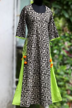 a long kurta in layers with handblock printed monochrome fabric & pop coloured inner layer. the layered kurta has tie-ups and woolen fumdas to add to the