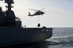 An MH-60 Sea Hawk helicopter lifts supplies from dry cargo and ammunition ship USNS Medgar Evers (T-AKE 13) during a vertical replenishment with guided-missile destroyer USS Ramage (DDG 61).