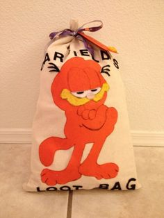 These were the give away treat bags I made for each child that attended the birthday.  I made them with actual heavy duck cotton bank money bags that I purchases online.  I made a paper pattern for Garfield and cut him out of felt and glued him on each bag. I cut letters out of felt and wrote Garfield's Loot Bag on each one. I tied them with Garfield ribbon I bought on Ebay, and made  tags out of card stock to attach each child's name.  These were a big success with are small guests.