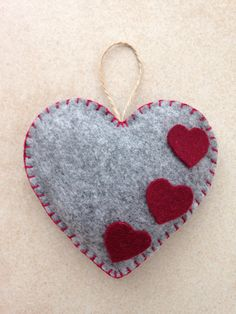 Items similar to Felt Heart Ornament, handmade on Etsy Saint Valentines day handmade hanging felt ornament. Colour: grey on the front and bourdeaux on the back. Decorated with three little bourdeaux felt hearts. Size: about x Felt Christmas Decorations, Felt Christmas Ornaments, Christmas Crafts, Etsy Christmas, Valentines Bricolage, Valentine Day Crafts, Little Presents, Fabric Hearts, Felt Embroidery