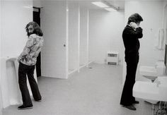 Richard Manuel and Robbie Robertson in the men's room during the Bob Dylan Tour. Denver, CO, 1974. Photo by Barry Feinstein.