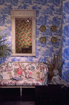 Villandry wallpaper by Cole & Son. Taking its name from the Chateau de Villandry which keeps one of the grandest gardens in France. This wallpaper design is printed in a classic Toile de Jouy style featuring a pastoral landscape of parkland, waterways and follies in four traditional colour-ways of red, soft charcoal, cobalt blue and dove grey. Sofa has been upholstered in wallpaper, Fontainebleau also from the Folie collection.