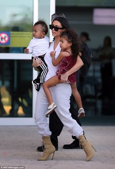 And they are off: Kim Kardashian showed some impressive mom skills as she carried both her babies in heels while moving at speed as they flew out of Costa Rica on Monday