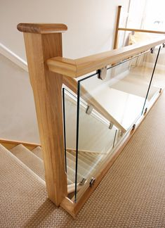 This oak and glass staircase looks spectacular and features Avon newel posts as well as brushed steel clamps to secure the beautiful glass panels. Staircase Glass Design, Wooden Staircase Railing, Interior Stair Railing, Modern Stair Railing, House Staircase, Stair Railing Design, Home Stairs Design, Stair Decor, Glass Railing