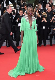 Lupita Nyong'o in a Gucci custom jade chiffon plisse gown, pink clutch, and green platform heels with Chopard jewelry at the 68th Annual Cannes Film Festival