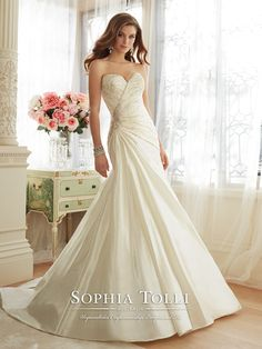 Strapless sweetheart dream taffeta fit and flare wedding dress, hand-beading highlights the asymmetrically draped bodice, sparkling beaded brooch on side, back corset, chapel length train. Removable spaghetti and halter straps included. Sizes: 0 – 28 Colors: Ivory, White