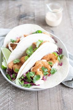 A crispy, crunchy and totally delicious recipe, these Coconut Shrimp Tacos are stuffed with cilantro cabbage slaw and a drizzle of spicy aioli. Healthy Taco Recipes, Honey Recipes, Wrap Recipes, Healthy Dessert Recipes, Seafood Recipes, Healthy Dinners, Healthy Food, Dinner Recipes, Healthy Shrimp Tacos