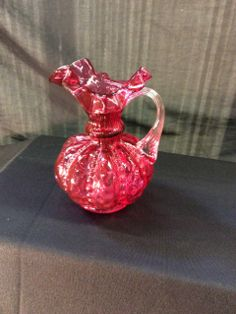 FENTON CRANBERRY GLASS WITH CLEAR HANDLE AND RUFFLED EDGE. THIS LOVELY PITCHER STANDS AT 7 IN. TALL. STAND NOT INCLUDED