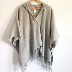 Juicy Couture Gray Hooded Blanket Cape Amazing 100% wool poncho by Juicy Couture. Magnetic closure in the front and under each arm. Great hood for rainy/snowy days and cutie fringe across the bottom. Like new condition. Comes with a large Juicy Couture pin to jazz up the front if you choose! Two tiny rhinestones in the pin are missing. Juicy Couture Jackets & Coats Capes
