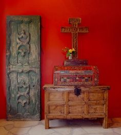 A great combination of a cross, an old door, a chest and an antique painted box.