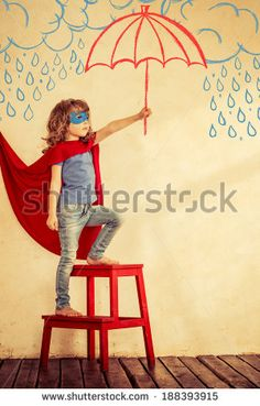 Full length portrait of superhero kid. Strong child against grunge wall background - stock photo