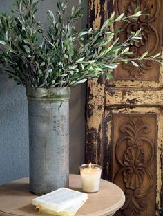 HGTV: Fixer Upper hosts Chip and Johanna Gaines add a brushed steel vase and candle to add rustic details to to the newly renovated living room.