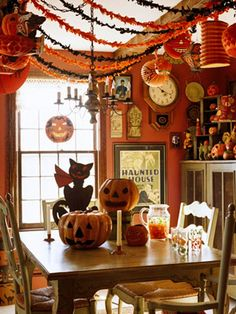 """""""The decor in this dining room is typical of 1920s party decorating with exotic paper lanterns, colorful streamers, and ghoulish pumpkin faces at every turn. The focal point of the dining room is a grinning Beistle black cat centerpiece that's nearly 80 years old."""""""