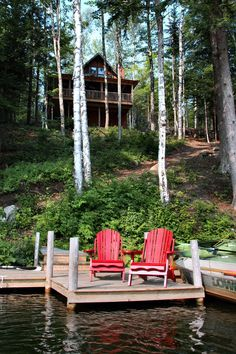 Red Adirondack chairs on dock at lake house.
