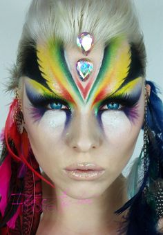 """Colorful tribal inspired fantasy make-up with two large teardrop crystals, titled """"Warrior"""" by Ida Aztor."""