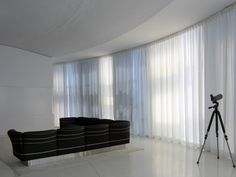 Motorized sheer pinch pleat curtains installed on a curved living room glass wall. Pinch Pleat Curtains, Pleated Curtains, Motorized Blinds, Interior Windows, Custom Window Treatments, Shades Blinds, Curved Glass, Custom Windows, Floor To Ceiling Windows