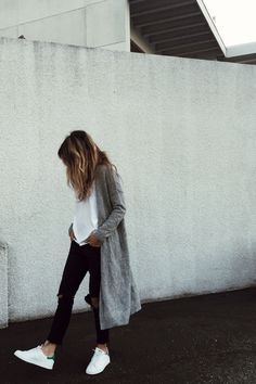 Ripped black denim with a white tee, long grey cardigan, and Stan Smiths.