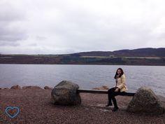 Foto do Lago Nesse e eu, sentada em um banco.