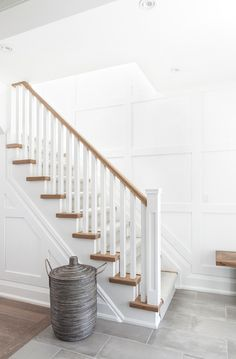 A light gray stripe runner accents a two-toned staircase boasting honey stained treads matching a honey stained handrail finished with white posts accenting a white board and batten wall. White Staircase, Staircase Runner, Staircase Remodel, Curved Staircase, Staircase Design, Oak Stairs, Wooden Stairs, House Stairs, Entrance Foyer