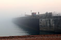 Sea Fog and the Prince of Wales Pier, Dover Harbour, Kent, England, UK. Far to the left, the entire Eastern Docks have been engulfed, and the fog creeps over the Hidden Houses of East Cliff there; a mile out to sea, the massive Southern Breakwater has suffered a similar fate. Only here in the west does part of the Admiralty Pier and this first section of the Prince of Wales Pier remain free. But not for long: the dense main mass has yet to arrive... See…