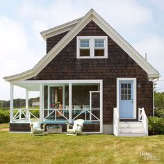Reflecting the color of the heavens above, a happy-hue door brings smiles aplenty. The sky blue door, the aqua accents on the porch, and the crisp white trim combine to give the brown-shingled cottage a cheerful lift./