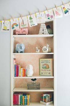 Pink Wallpaper Bookcase Read More: http://www.stylemepretty.com/living/2014/10/30/traditional-meets-cozy-home-tour-in-long-island/