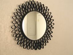 Spray paint frame of round mirror black and smash toilet paper rolls (yes,really) flat. Cut flattened tp rolls to make leaf shapes. Paint each leaf shape with black paint. Using hot glue gun or other good adhesive, glue the leaves around the mirror until finished.