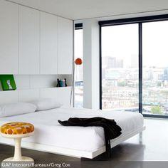 Eine praktische und elegante Lösung ist die weiße Schrankwand hinter dem Doppelbett. Durch die übrigen weißen Wände fällt der Schrank hinter dem Bett kaum…