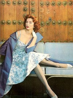 Suzy Parker in a cocktail dress and taffeta coat in shades of blue as seen in Vogue, Apr. 1958