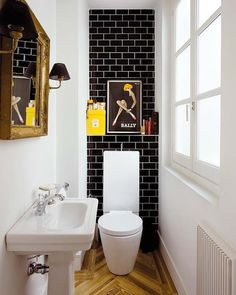 Tiny powder room with black Subway Tile and white grout. Herringbone floors.