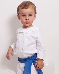 Camisa de bebé con cuello marinero y manga larga en oxford blanco, junto con unas bermudas oxford blanco y un fajín de ceremonia con nudo en lino azulón.