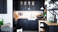 Traditionelle dunkle METOD Küche mit LAXARBY Fronten, Vitrinentüren und Deckseiten in Schwarzbraun, Massivholzarbeitsplatten und verchromter EDSVIK Zweigriff-Mischbatterie/Küche