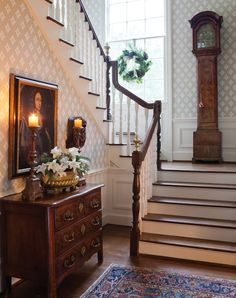 A silver container filled with alabaster lilies and evergreen sprigs and a woodland-inspired wreath at the window complement the stately antiques and furnishings of the foyer.                                                                                                                                                                                 More