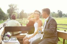 Bride and groom in horse drawn wagon with sun flare  Heidi Burks Photography