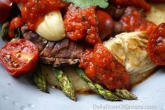 Grilled vegetables are served stacked over creamy polenta and topped with a flavorful, fire-roasted tomato and red pepper harissa.
