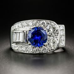 A beautiful round faceted royal blue sapphire, weighing 2.34 carats, beams from the center of this bold and striking original Art Deco jewel, hand-fabricated in platinum - circa 1930s. The high-profile multidimensional mounting features a raised row of baguettes culminating in a pair of larger European-cut diamonds, bringing the total weight of bright-white sparkling diamonds to 1.65 carats. Singular and sensational! Currently ring size 7.