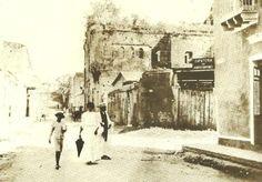 1904 - La calle Hostos antes de 1904 era denominada del Hospital, por las Ruinas el Hospital San Nicolás de Bari que aparecen en esta fotografía. Dicho hospital fue construido entre 1503 y 1552 pero, ya para 1821, era una ruina. En 1911 fue demolido casi totalmente por considerarsele un peligro público