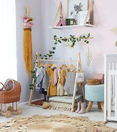 Une jolie penderie pour bébé fille avec un portant en bois dans sa chambre