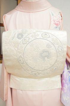 白地に銀の糸が霞のように織り込まれた白銀の地に、ぽつんと丸い結び玉が連なる相良刺繍を思わせる大輪の花の装飾円模様が浮かび上がるロマンチック・エレガントなお太鼓柄の袋帯です。