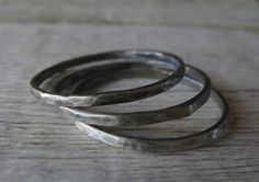 This minimalist set of 3 thin sterling silver hammered stacking rings make a delicate statement. The little facets add interest to the rustic finish. Available in multiple finish options in our shop. All sizes are in US ring sizes. - Thin sterling silver hammered stacking rings - Available in US sizes 4 - 16 - Handmade in the USA - Delivered in a small gift box - Bands measures 1.2mm thick - Made to order - Requires up to 14 business days prior to shipment