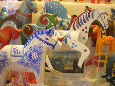 Visit the birthplace of Dala horses - Dararna, Sweden.  This is the first of a two part series. I am loving this image of vintage Dala's on display at the factory. I adore the white and blue Dala horse!