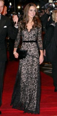 01/08/2012 - Kate wore an on-trend black lace gown with a nude-lined underlay and velvet belt by one of her favorite British designers, Alice Temperley.  Middleton accessorized with a matching velvet bow clutch by Mascaró, her diamond & sapphire engagement ring, & a diamond bracelet.  Prince William looked ever the gentleman in a tuxedo & bow tie while holding the umbrella over Kate.