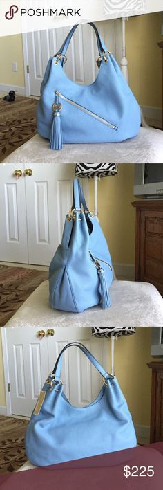 "Authentic MK Charm Tassel Large Leather Shoulder Authentic MK Charm Tassel Large Leather Shoulder Tote Bag. Style # 38S6XTSE3L. Color- Powder Blue w/ gold plated hardware. New with tag. Dimensions- 16.5"" L x 10.75"" H x 4"" W and handle drop height of 8-9"". Magnetic top closure with mk signature inside fabric lining & zip/multifunction pockets. Has front zip closure pocket with MK charm tassel. See picture for more details of the purse. No dust bag available. Note- the last picture is the same…"