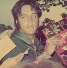 Elvis signing his NBC TV Special Album for a lucky fan