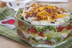 What To Do:      In a medium bowl, combine mayonnaise, sour cream, and garlic powder; mix well.           In a large glass bowl (see Note), layer half the lettuce then half the red peppers, onion, green peas, celery, mayonnaise mixture, and cheese.           Repeat layers then top with bacon bits. Cover and chill for at least 2 hours before serving (see Note).