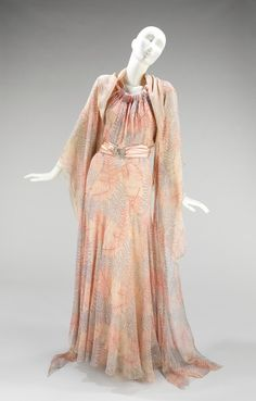 Vionnet | c. 1936  Layers of gossamer, yet strong, silks cut on the bias, with free-floating ties, make this evening dress an exemplar of Vionnet's work. The design also features a pastel foliate print of the type favored by the designer, here with a pattern of fern leaves. The satin ties of the dress were originally held by a jade buckle, which was not received with the gift.