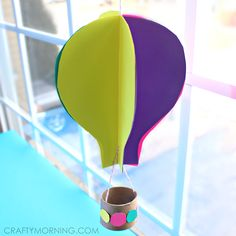 Make a 3d hot air balloon craft with your kids using paper and toilet paper rolls.